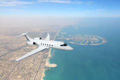 Business jet airplane flying over Dubai city and sea coastline.  Stock Photography