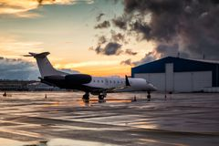 Business jet at sunset after the rain on the airport apron near the hangar. Corporate jet at sunset after the rain on the airport apron near the hangar royalty free stock photo