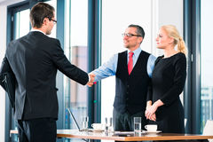 Business - Job Interview and hiring. Business - young men in job interview for hiring, welcomes, Boss or Senior and his female Assistant in their office Stock Image