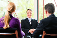 Business - Job Interview with HR and applicant. Business - young man as applicant sitting in job interview with future boss and HR royalty free stock photo