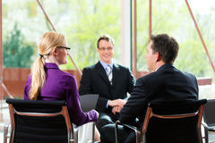 Business - Job Interview with HR and applicant. Business - young man as applicant sitting in job interview with future boss and HR stock image
