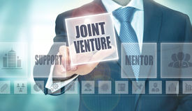 Business Joint Venture Concept. A businessman pressing a Joint Venture button on a transparent screen Royalty Free Stock Images