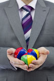 Business Juggler. Studio Isolation of a single caucasian male. He is holding 3 Juggling balls in front of him. A conceptual image to display juggling in business Royalty Free Stock Photography