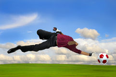 Business-keeper. Businessman playing soccer outdoors in a green field stock photo