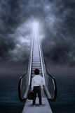Business kid at escalator under clouds Royalty Free Stock Photos