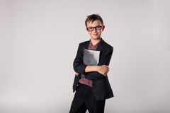 Business kid holding laptop in his hands. Portrait of cute business kid in a suit and eyeglasses holding laptop in his hands Stock Photo