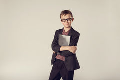 Business kid holding laptop in his hands. Portrait of cute business kid in a suit and eyeglasses holding laptop in his hands Stock Photos