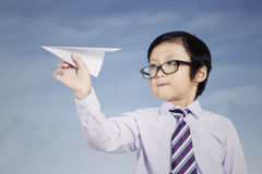 Business kid holding paper airplane outdoor Stock Image