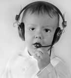 Business kid in telephone ear-phones. Serious little boy in ear-phones with a microphone in call center answers a call on a white background Royalty Free Stock Image