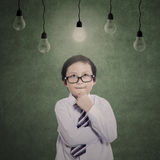 Business kid thinking under lit bulbs Royalty Free Stock Photos