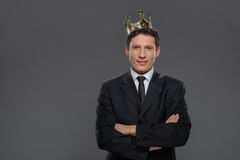 Business king. Confident businessman in crown standing isolated. On gray with his arms crossed royalty free stock photo