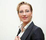 Business lady. Portrait of a lovely successful business woman smiling over white background royalty free stock photography