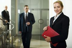 Business lady. Smart beautiful businesswoman with red case in her hands and two men behind her going downstairs Stock Photography