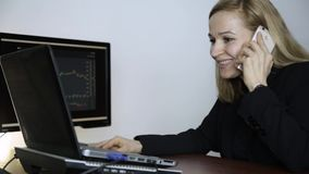 Business lady advises client on a phone and watching currency exchange chart at the computer monitor. Work on a crypto. Businesslady talking on a phone and stock video footage