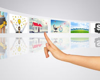 Business lady and buildings. Finger presses one of Royalty Free Stock Photos