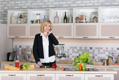 Business Lady cooking Food and talking on Telephone Stock Photography