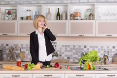 Business Lady cooking Food and talking on Telephone Royalty Free Stock Photos