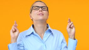 Business lady crossing fingers for good luck and looking up, project success. Stock footage stock video footage