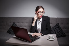 Business lady dressed in suit and with laptop has a coffee break Royalty Free Stock Photography