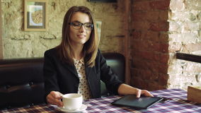 Business lady in glasses drinking coffee, using a tablet and smiling in cafe 4k stock footage