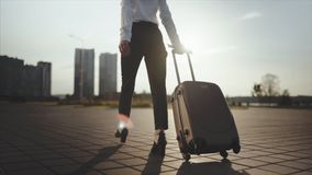 Business lady going to taxi parking from the airport with her luggage. Girl in heels stepping and roll suitcase on. Close up, Knee or ground level shot: Business stock video