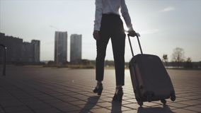 Business lady going to taxi parking from the airport with her luggage. Girl in heels stepping and roll suitcase on. Close up, Knee or ground level shot: Business stock footage