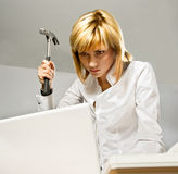 Business Lady with a Hammer. Angry business lady hitting a laptop with a hammer royalty free stock image