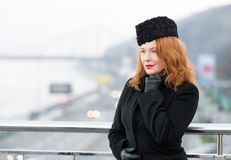 Portrait of business lady has rest on balcony. Aged women model in black coat and gloves. Woman on bridge waiting for meeting. Royalty Free Stock Photos