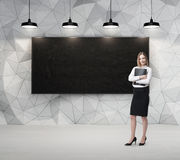 Business lady is holding a black document case. Blank blackboard on the background. Royalty Free Stock Image