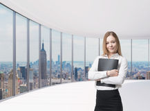 Business lady is holding a black document case. New York panoramic office. A concept of legal services. Young beautiful business lady is holding a black stock photography