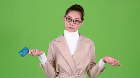 Business lady holding a credit card in her hands has no money. Green screen. Slow motion stock footage