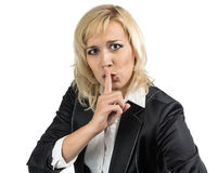 Business lady holding her finger near the mouth. Business lady in suit holding her finger near the mouth Royalty Free Stock Photos