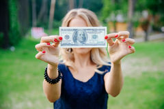 Business lady holds hundred dollars in the face of. Business Woman Hold Banknote One Hundred Dollars in Hand. Close face dollar banknote. Business concept Stock Image