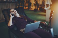 Business lady is laying on massage chair during coffee break royalty free stock photo