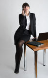 Business Lady leaning at desk takling on the mobile phone Royalty Free Stock Photo