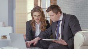 Business lady and man check presentation on laptop, slow motion stock footage