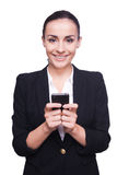 Business lady with mobile phone. Cheerful young woman in formalwear holding mobile phone and smiling while standing isolated on white Stock Photos
