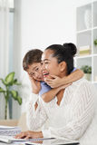 Business lady and mother. Asian business lady laughing when her son hugging her Royalty Free Stock Photography