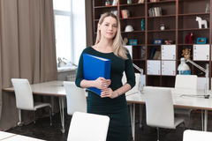 Business lady is in the office with a folder in hands. Woman standing in office and holding a folder in his hands. Looking at the frame and smiles Stock Photos