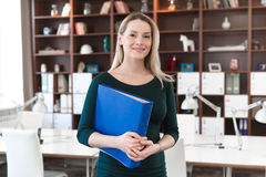Business lady is in the office with a folder in hands. Woman standing in office and holding a folder in his hands. Looking at the frame and smiles Royalty Free Stock Image