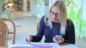 Business lady with phone and charts in cafe stock video footage
