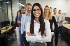 Business lady with positive look and cheerful smile posing for camera. In front of her colleagues Stock Photo