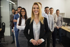Business lady with positive look and cheerful smile posing for camera. In front of her colleagues Stock Photos