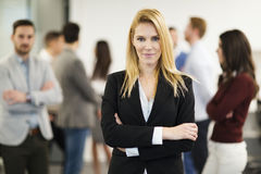 Business lady with positive look posing for camera. In front of her colleagues Stock Images