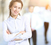 Business lady with a positive outlook and cheerful smile posing for the camera, in the background  team. Business lady with positive look and cheerful smile Stock Image