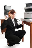 Business lady with a printer. Pretty business lady or student clearing a printer paper jam and throwing jammed paper towards the viewer royalty free stock image