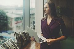 Businesswoman with laptop next to office window stock photos