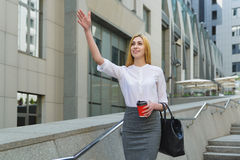 Business lady raised her hand and waves to someone stock photography