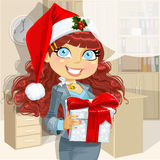 Business lady in Santas cap gives a gift Stock Images
