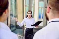 Business lady screams at subordinates. Conversation on high tone royalty free stock photo